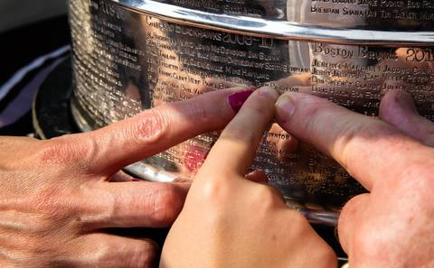 Whitney Parchman and her husband Troy show his name engraved on the Stanley Cup to their 6-year-old son Evan on board the Anita D II at Navy Pier.