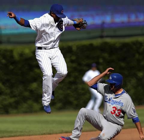 Cubs shortstop Starlin Castro tries to avoid falling on Dodgers baserunner Scott Van Slyke.