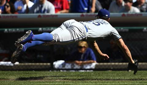 Dodgers starting pitcher Chris Capuano dives after making a throw to first.