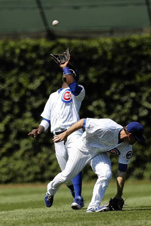 Cubs left fielder Junior Lake makes a catch over Donnie Murphy during the fourth inning.