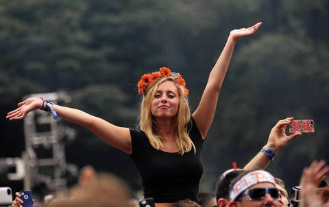 A Disclosure fan waves her arms while sitting on someone's shoulders during the band's performance at Lollapalooza.