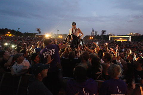 A fan on a wheelchair is surfed through the crowd during the Nine Inch Nails performance at Lollapalooza.