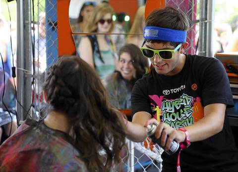 Frankie Rodriguez, 22, right, colors the tips of 20-year-old Kate Emerson's hair with gold spray in the Toyota tent as Lollapallooza opens in Chicago's Grant Park on Friday.
