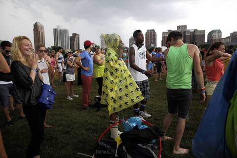 Concert-goers cover up during an afternoon rain shower while watching Icona Pop.