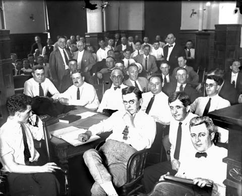 The above picture was taken on July 5, 1921 in Judge Friend's courtroom while an effort was being made to obtain a jury to try the accused members of the White Sox baseball team of 1919, charged with having 'thrown' games in the World Series of that year. Those shown in the picture are Attorney Thomas D. Nash, lower right, Attorney James C. O'Brien, second from lower right, and Attorney Ben Short, center at desk. The front row of men in white shirts and ties are all attorneys. White Sox players are in the row behind the Attorneys in suits, from right to left, including Chick Gandil, (not shown), Oscar 'Happy' Felsch, Charles 'Swede' Risberg, George 'Buck' Weaver, Eddie Cicotte, Joe Jackson and Claude 'Lefty' Williams.
