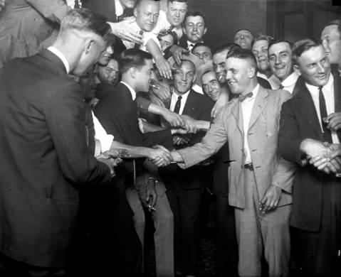 Chicago White Sox players are congratulated after their acquittal in the Black Sox trial of 1921. Eddie Cicotte, second from right front, and Oscar 'Happy' Felsch, right, shake hands with fans as George 'Buck' Weaver (center with hat) and several other players and fans smile for the camera.