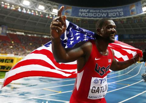 Justin Gatlin of the U.S. holds his national flag as he celebrates finishing in second place in the men's 100 meters final during the IAAF World Athletics Championships at the Luzhniki stadium in Moscow August 11, 2013.