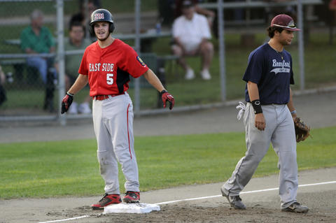 Center fielder Joe Consolmagno. 5, of Worcester, reacts after hitting a two out triple in the top of the first inning as third baseman Greg Zullo, 7, of Branford, walks back to his position.