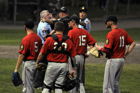 Worcester's manager Daniel Generelli, argues with the umpires as his team waits for the verdict on the last play of the game after Branford's team celebrated a successful suicide squeeze play in the bottom of the second inning. The run gave Branford the win because of the mercy rule, but the batter didn't make it to first base because he was piled on by his team.