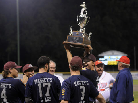 Branford's pitcher John Amendola, 10, hoists the trophy into the air after the game.