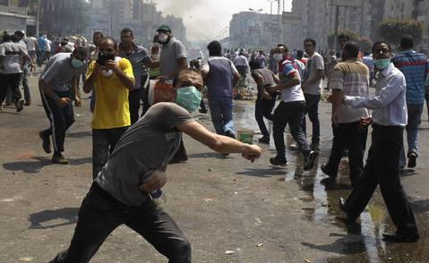 Members of the Muslim Brotherhood and supporters of ousted Egyptian President Mohamed Mursi throw stones at riot police and army personnel during clashes around the area of Rabaa Adawiya square, where they are camping, in Cairo August 14, 2013. The death toll from an Egyptian police raid on supporters of deposed President Mohamed Mursi at a Cairo protest camp has climbed to 60 at one hospital, according to a nurse who said she counted the bodies. REUTERS/Asmaa Waguih