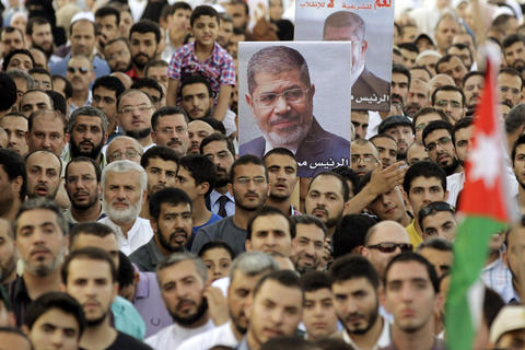 Protesters from the Islamic Action Front take part in a rally in support of deposed Egyptian president Mohamed Mursi (poster) near the Egyptian embassy in the Jordanian capital Amman, on August 14, 2013, after Egyptian security forces supported by bulldozers moved in on two huge pro-ousted president Mohamed Morsi protest camps in the Egyptian capital Cairo, launching a long-threatened crackdown and leaving scores dead. KHALIL MAZRAAWI/AFP/Getty Images