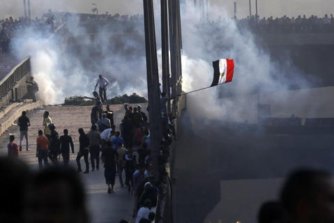 Members of the Muslim Brotherhood and supporters of ousted Egyptian President Mohamed Mursi flee from tear gas and rubber bullets fired by riot police during clashes, on a bridge leading to Rabba el Adwia Square where they are camping, in Cairo August 14, 2013. At least 95 Egyptians were killed on Wednesday after security forces moved in on protesters demanding the reinstatement of Mursi, and the government imposed a state of emergency as unrest swept the most populous Arab nation. REUTERS/Amr Abdallah Dalsh
