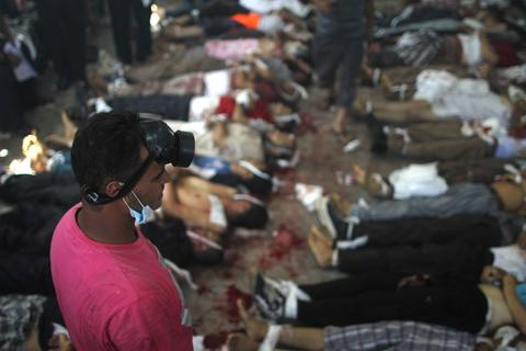 TOPSHOTS A man looks at bodies laid out in a make shift morgue after Egyptian security forces stormed two huge protest camps at the Rabaa al-Adawiya and Al-Nahda squares where supporters of ousted president Mohamed Morsi were camped,  in Cairo, on August 14, 2013. Egypt's bloody crackdown on supporters of  Morsi triggered widespread condemnation as the international community reacted with alarm to the deepening crisis. The action has resulted in more than 120 deaths, according to AFP reporters at the scene.  MOSAAB EL-SHAMYMOSAAB EL-SHAMY/AFP/Getty Images