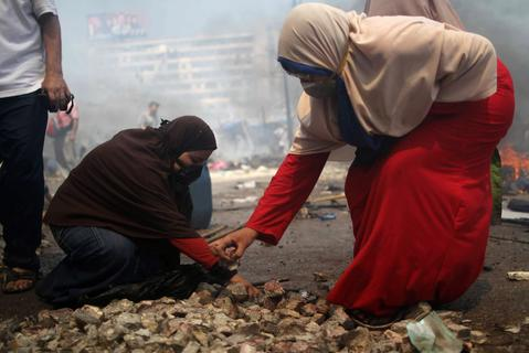 A female supporters of the Muslim Brotherhood and Egypt's ousted president Mohamed Morsi gather stones during clashes with police in Cairo on August 14, 2013, as security forces backed by bulldozers moved in on two huge pro-Morsi protest camps, launching a long-threatened crackdown that left dozens dead. The clearance operation began shortly after dawn when security forces surrounded the sprawling Rabaa al-Adawiya camp in east Cairo and a similar one at Al-Nahda square, in the centre of the capital. MOSAAB EL-SHAMY/AFP/Getty Images