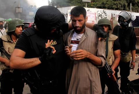 An Egyptian policeman helps a wounded demonstrator during clashes as security forces dispersed protest camps on August 14, 2013 that were set up in Cairo by supporters of Egypt's ousted president Mohamed Morsi. The clearance operation began shortly after dawn when security forces surrounded the sprawling Rabaa al-Adawiya camp in east Cairo and a similar one at Al-Nahda square, in the centre of the capital. HASSAN MOHAMED/AFP/Getty Images