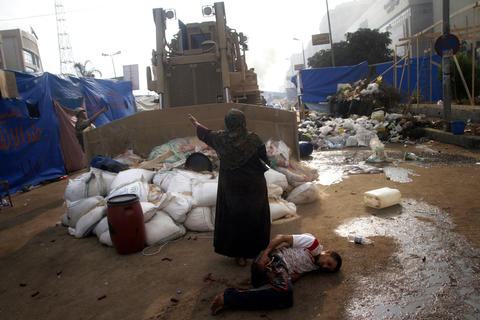 An Egyptian woman tries to stop a military bulldozer from hurting a wounded youth during clashes that broke out as Egyptian security forces moved in to disperse supporters of Egypt's deposed president Mohamed Morsi in a huge protest camp near Rabaa al-Adawiya mosque in eastern Cairo on August 14, 2013. The operation began shortly after dawn when security forces surrounded the sprawling Rabaa al-Adawiya camp in east Cairo and a similar one at Al-Nahda square, in the centre of the capital, launching a long-threatened crackdown that left dozens dead. MOHAMMED ABDEL MONEIM/AFP/Getty Images