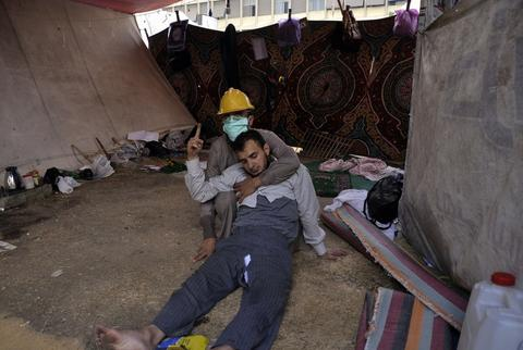 A masked man helps a wounded fellow protester inside a tent as Egyptian security forces move in to disperse supporters of Egypt's ousted president Mohamed Morsi by force in a huge camp in Cairo's Al-Nahda square on August 14, 2013. The operation began shortly after dawn when security forces surrounded the sprawling Rabaa al-Adawiya camp in east Cairo and a similar one at Al-Nahda square, in the centre of the capital, launching a long-threatened crackdown that left dozens dead. Engy Imad/AFP/Getty Images