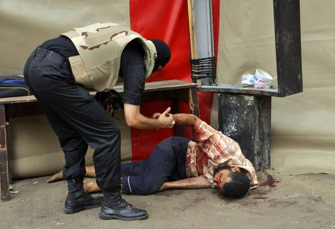 A member of the Egyptian security forces helps a wounded man in Cairo's Al-Nahda square after police forces moved in to disperse supporters of Egypt's ousted president Mohamed Morsi in two huge protest camps in the Egyptian capital by force on August 14, 2013. The operation began shortly after dawn when security forces surrounded the sprawling Rabaa al-Adawiya camp in east Cairo and a similar one at Al-Nahda square, in the centre of the capital.  Engy Imad/AFP/Getty Images