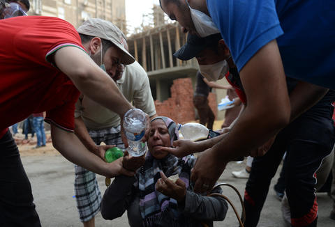 Egyptians help a woman suffering from tear gas exposure after canisters were fired by Egyptian police as they try to disperse a pro-Morsi camp in a street leading to Rabaa al-Adawiya in Cairo on August 14, 2013. Egypt's Muslim Brotherhood said at least 250 people were killed and over 5,000 injured in a police crackdown on two major protest camps held by supporters of ousted president Mohamed Morsi. KHALED DESOUKI/AFP/Getty Images