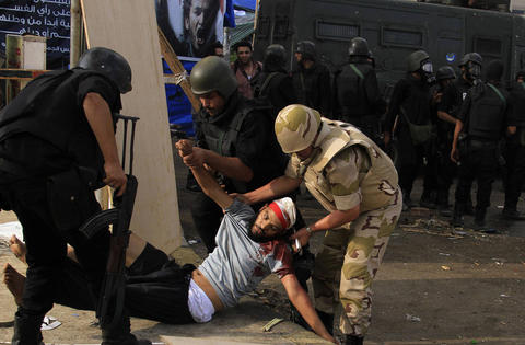 An injured member of the Muslim Brotherhood and supporter of deposed Egyptian President Mohamed Mursi is carried by members of the riot police and the army after they cleared Rabaa Adawiya square area, where the Pro-Mursi supporters are camping, in Cairo August 14, 2013. Egyptian security forces killed at least 30 people on Wednesday when they cleared a camp of Cairo protesters who were demanding the reinstatement of Mursi, his Muslim Brotherhood movement said.