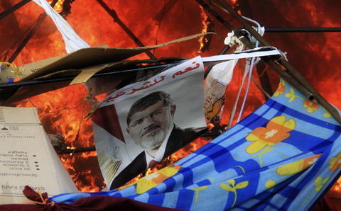 "A poster of Mursi reads ""Yes to legitimacy."" as riot police clear the area of members of the Muslim Brotherhood and supporters of deposed Egyptian President Mohamed Mursi, at Rabaa Adawiya square, where they are camping, in Cairo August 14, 2013. Egyptian security forces killed at least 30 people on Wednesday when they cleared a camp of Cairo protesters who were demanding the reinstatement of Mursi, his Muslim Brotherhood movement said."