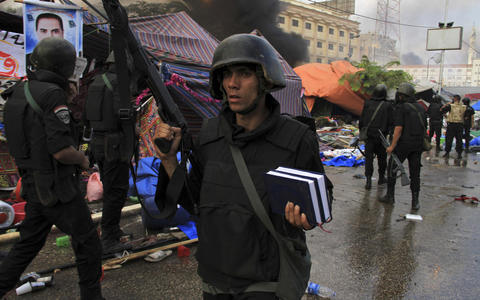 A riot police officer holds a copy of the Koran as they clear the area of members of the Muslim Brotherhood and supporters of deposed Egyptian President Mohamed Mursi, at Rabaa Adawiya square, where they were camping, in Cairo August 14, 2013. Egyptian security forces killed at least 30 people on Wednesday when they cleared a camp of Cairo protesters who were demanding the reinstatement of Mursi, his Muslim Brotherhood movement said.