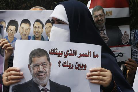 "A Lebanese Muslim woman from the Sunni Al Jama'a al-Islamiya group carries a picture of deposed Egyptian President Mohamed Mursi during a protest in support of him near the Egyptian embassy in Beirut August 14, 2013. Egyptian security forces killed at least 30 people on Wednesday when they moved in to clear a camp of Cairo protesters demanding the reinstatement of deposed President Mohamed Mursi, his Muslim Brotherhood movement said. The words read, ""What is the secret between you and God."""
