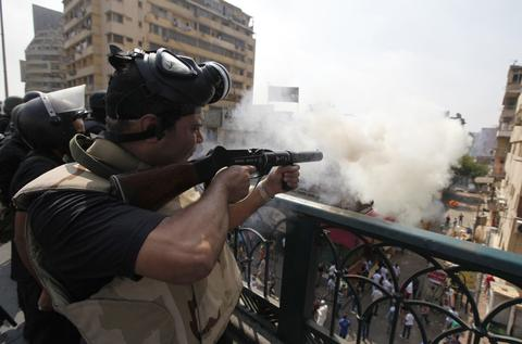 Riot police fire tear gas during clashes with members of the Muslim Brotherhood and supporters of deposed Egyptian President Mohamed Mursi, around Cairo University and Nahdet Misr Square, where they are camping in Giza, south of Cairo August 14, 2013. Egyptian security forces killed at least 30 people on Wednesday when they cleared a camp of Cairo protesters who were demanding the reinstatement of Mursi, his Muslim Brotherhood movement said.