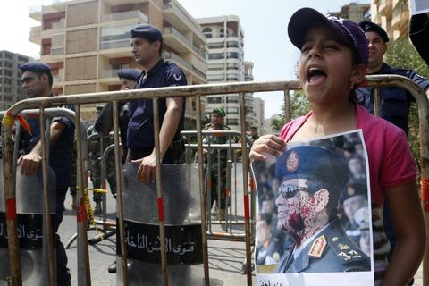 A girl carries a portrait of Egyptian army chief General Abdel Fattah al-Sissi and shouts slogans as policemen and army soldiers stand guard during a protest organised by the Sunni Al Jama'a al-Islamiya group in support of Egyptian President Mohamed Mursi near the Egyptian embassy in Beirut August 14, 2013. Egyptian security forces killed at least 30 people on Wednesday when they moved in to clear a camp of Cairo protesters demanding the reinstatement of deposed President Mohamed Mursi, his Muslim Brotherhood movement said.