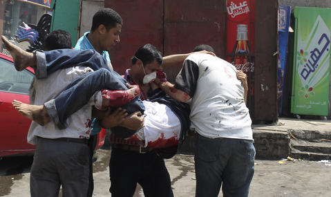 Supporters of deposed Egyptian President Mohamed Mursi carry a protester injured during clashes with riot police and the army at around the area of Rabaa Adawiya square, where they are camping, in Cairo August 14, 2013. The death toll from an Egyptian police raid on supporters of deposed President Mohamed Mursi at a Cairo protest camp has climbed to 60 at one hospital, according to a nurse who said she counted the bodies.