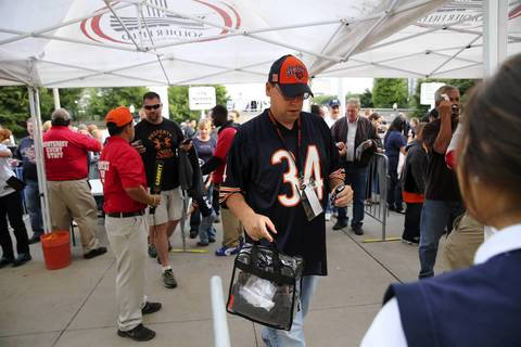 A Bears fan carries a clear plastic bag while going through a new security measure while entering Soldier Field.