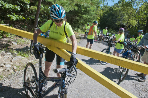 2013.08.15 - Thompson, CT - Cyclist Deb Haas of Coventry maneuvers her bicycle around a gate at the start of the Air Line State Park Trail in Thompson after she and about 20 others began an 11-day trek through Connecticut to commemorate the centennial of its State Park system.