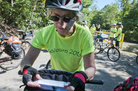 2013.08.15 - Thompson, CT - Cyclists Joan Samson checks her map at the start of the Air Line State Park Trail in Thompson after she and about 20 others began an 11-day trek through Connecticut to commemorate the centennial of its State Park system.