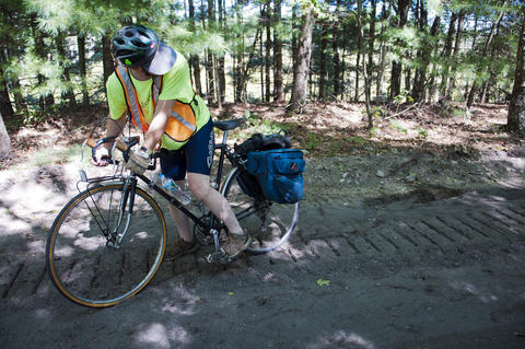2013.08.15 - Thompson, CT - Cyclist Tom O'Conner of Tolland examines his rear wheel after getting nudged off his bike by a rough section of the Air Line State Park Trail on the of an 11-day trek through Connecticut to commemorate the centennial of its State Park system.