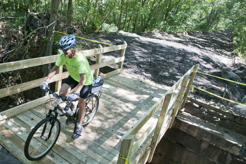 2013.08.15 - Thompson, CT - Katie Young of Monroe, Ct, crosses a newly constructed bridge along the Air Line State Park Trail as she and about 20 cyclists begin an 11-day trek through Connecticut to commemorate the centennial of its State Park system.