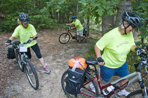 2013.08.15 - Thompson, CT - (L-R) Diane Joy, Al Levere and Tess Gutowski portage through a steep section of the Air Line State Park Trail as they and about 20 cyclists begin an 11-day trek through Connecticut to commemorate the centennial of its State Park system.