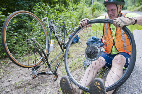 2013.08.15 - Thompson, CT - Tom O'Conner repairs a flat tire along the Air Line State Park Trail on the first day of an 11-day journey he and about 20 cyclists will make to commemorate the centennial of Connecticut's State Park system.