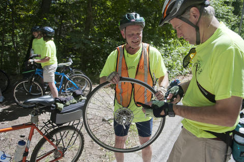 2013.08.15 - Thompson, CT - Tom O'Conner (L) gets help repairing a flat from Scott Young of Orange along the Air Line State Park Trail on the first day of an 11-day journey he and about 20 cyclists will make to commemorate the centennial of Connecticut's State Park system.