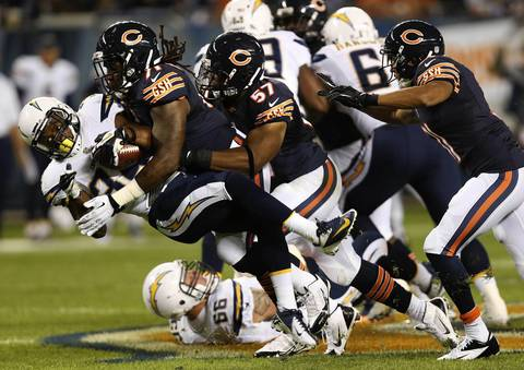 Aston Whiteside, and Jon Bostic (57) take down Chargers running back Fozzy Whittaker in the second quarter.