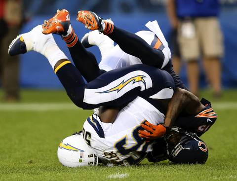 Brandon Marshall tackles Chargers linebacker Donald Butler after Butler intercepted a pass in the first quarter.