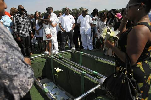 A flower is tossed towards the caskets of slain brothers LeAndre and Demetrius Cooper of Chicago as their caskets are lowered into the ground during their funeral at Burr Oak Cemetery in Alsip. The brothers were shot and killed on August 6th in the West Pullman neighborhood.