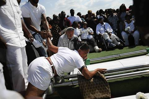 A mourner is pulled up after she laid on top of the caskets of slain brothers LeAndre and Demetrius Cooper of Chicago as they were lowered into the ground during their funeral at Burr Oak Cemetery in Alsip.