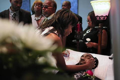 Latayna Herring gently touches her son Jacobi during his funeral at Unity Funeral Parlor in Chicago. 21-year-old Jacobi was shot and killed on Aug. 10.
