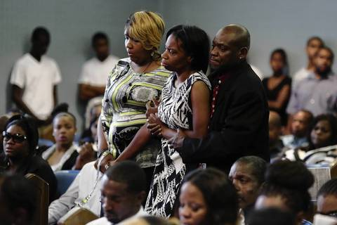 Latayna Herring, center, whose son Jacobi Herring was shot and killed on Aug. 10, is helped back to her seat by loved ones after becoming emotional during his funeral.