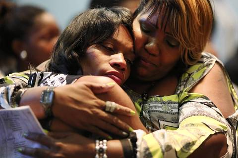 Latayna Herring, left, whose son Jacobi Herring was shot and killed on Aug. 10, is comforted by her friend during his viewing.