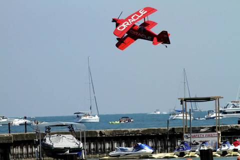 Sean Tucker flies his bi-wing Oracle Challenger low over the boats in Lake Michigan at the Chicago Air and Water show.