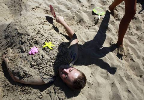 Jeremy Mrazek, 15, of New Lenox is covered in sand at North Avenue Beach during the Chicago Air and Water Show.