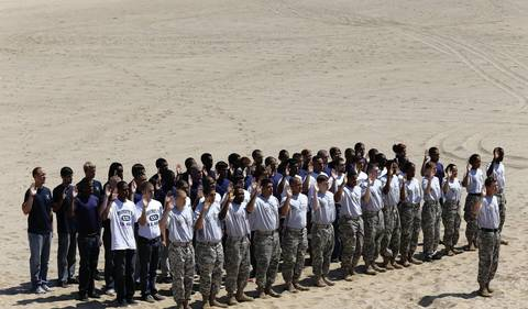 A group of military recruits make their pledge in a swearing-in ceremony at North Avenue Beach during the Chicago Air and Water show.