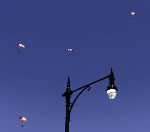 A team of parachuters descends onto North Avenue Beach during the Chicago Air and Water show.